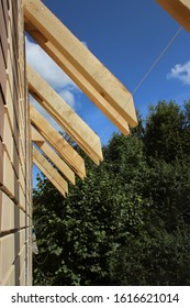 Roof trusses not covered with ceramic tile on a detached house under construction, visible roof elements, battens, counter battens, rafters. Industrial roof system with wooden timber, beams
