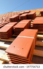 A roof under construction with stacks of roof tiles