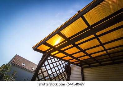 The roof of the veranda of orange polycarbonate on blue sky background.
