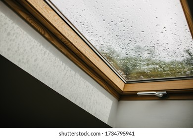 Roof window with rain drops on a glass