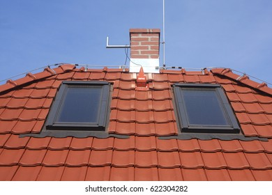 Roof windows, red clay tiles, chimney and lightning