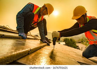 The roof work team in work clothes and special protective gloves using air guns or air nails and install asphalt or tar on the new roof under the residential building.