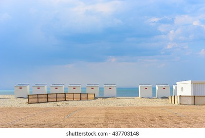 Roofed beach chairs at ocean of Nieuwpoort in Belgium / Sandy coast of North Sea / Vacation in northern europe