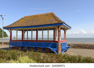 roofed blue bench at Minehead, Somerset view of a gazebo built on a blue  bench on seaside promenade at historic touristic village of  Somerset. Shot in bright light