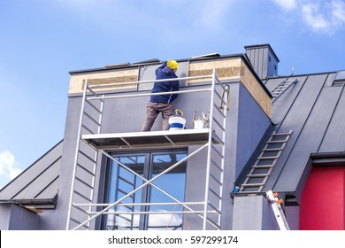 Roofer assembles sheet metal on the roof. Roofers on the roof.