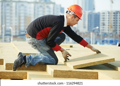 Roofer builder worker installing roof insulation material