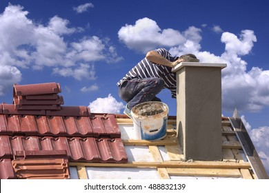 Roofer builder worker repairing a chimney stack on a roof house