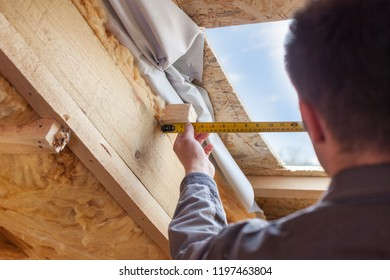 Roofer builder worker with ruler install plastic (mansard) or skylight window on attic with environmentally friendly and energy efficient thermal insulation rockwool