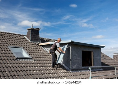 Roofer carrying a metal piece through the rooftop to the dormer wall