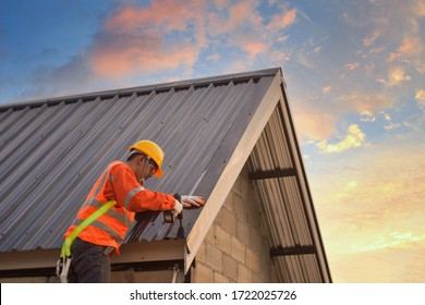 Roofer Construction worker install new roof,Roofing tools,Electric drill used on new roofs with Metal Sheet. - Shutterstock ID 1722025726
