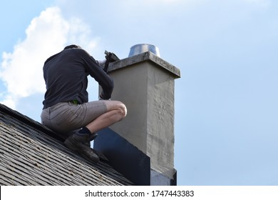 Roofer construction worker repairing chimney on grey slate shingles roof of domestic house, blue sky background with copy space.