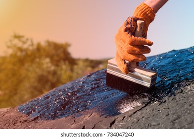 Roofer cover the concrete base, polymer modified bitumen waterproofing primer. A worker brushes cover concrete, bitumen-rubber primer. Waterproof roof. Bitumen waterproofing