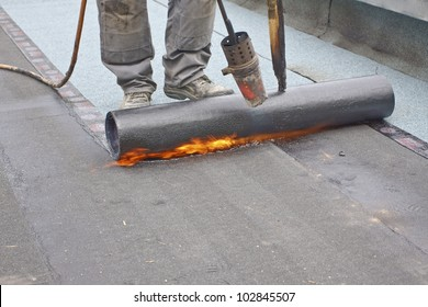 A roofer covering a roof with roofing felt.