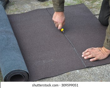 Roofer cutting roll roofing felt or bitumen during waterproofing works. Roofing repair.