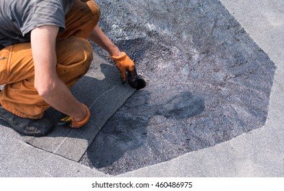 Roofer doing repair  roof drain. Flat roof installation. Heating and melting bitumen roofing felt. Flat roof repairing with roofing felt. Professional master , making waterproofing.