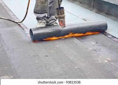 A roofer with a gas burner and a roll of tar paper