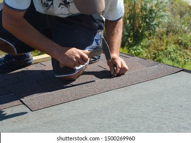 Roofer with hammer and nails laying asphalt shingles tiles on house roof. Roofing Construction