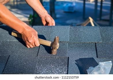 Roofer installing corner bitumen roof shingles with hammer and nails.