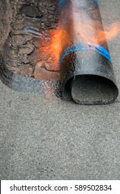 Roofer installing Roofing felt with heating and melting of bitumen roll by torch on flame during roof repair. Workers installing roofing felt with heat. Waterproofing
