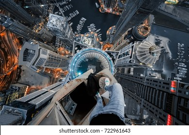 Roofer legs on rooftop of skyscraper in illuminated Dubai Marina area with water channel at night