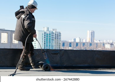 Roofer man worker at building site installing roll of roofing felt with gas blowpipe torch during construction works