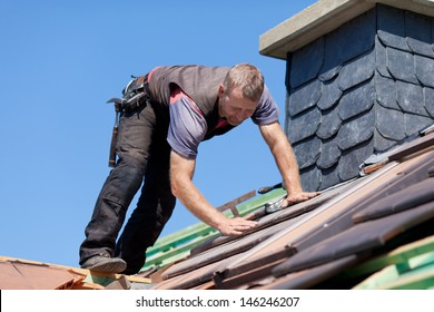Roofer next to the chimney verifying the tiles