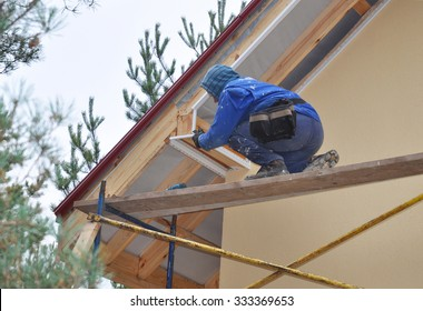 Roofer on the Corner of House  Install Soffit. Roofing Construction. Soffit and Fascia is Usually Constructed of Vinyl, Wood or Aluminum and is Installed on the Underside of Roof Overhangs and Eaves.