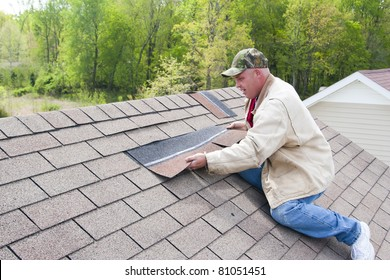 Roofer repairing damaged shingles after a storm with very high winds came through over night