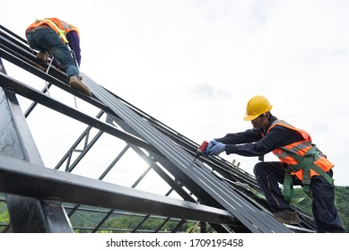 The Roofer technicians work on the roof structure of the building at the construction site. Roofer uses an electric drill and installs a metal sheet on the new roof.