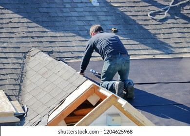 A roofer uses a nail gun to apply tarp to a roof in preparations for shingling.