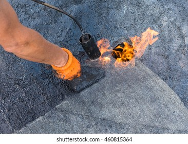 Roofer warms up and brushes shale coating to enhance adhesion when gluing roll material  together. Roofer doing repair  roof drain. Flat roof installation.