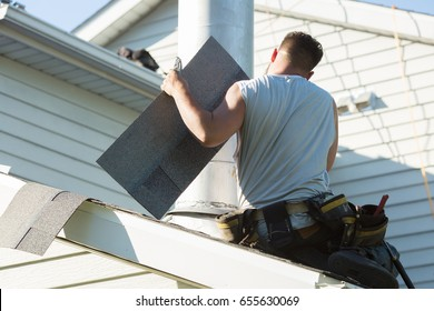 Roofer at work installing new roof on home
