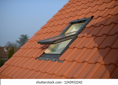 roofer work of a roof area window: velux style roof light window in red tiles