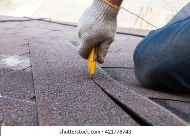 Roofer worker cuts shingles on the roof