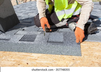 Roofer worker cuts shingles witk scissors on the roof