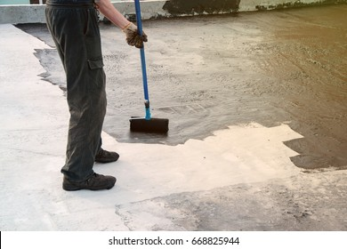 Roofer worker painting  bitumen praimer at concrete surface by the roller brush. Waterproofing. Copy space. Space for text.
