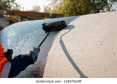 Hoe on the wet tar roof ax