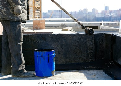 Roofer worker painting black coal tar or bitumen at concrete surface by the roller brush