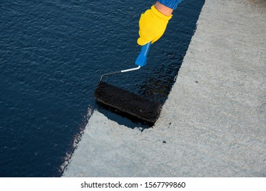Roofer worker painting black coal tar or bitumen at concrete surface by the roller brush, A waterproofing. industrial worker on construction site laying sealant for waterproofing cement