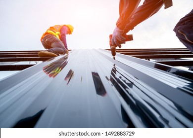 Roofer worker in protective uniform wear and gloves, using air or pneumatic nail gun and installing asphalt shingle on top of the new roof,Concept of residential building under construction.