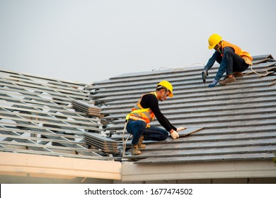 Roofer worker in special protective work wear and gloves,Using pneumatic gun and installing concrete roof tile on top of the new roof,Concept of residential building under construction.