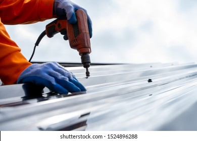 Roofer worker using air or pneumatic nail gun and installing metal sheet on top of the new roof.