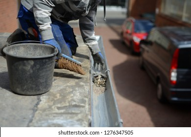 roofer working on roof maintenance. Clean zinc gutter with blue working gloves and hand brush