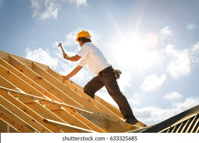 roofer working on roof structure of building on construction site