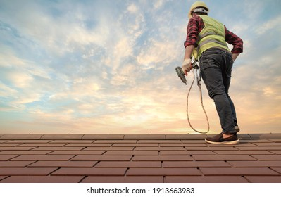 Roofer working in special protective work wear gloves, using air or pneumatic nail gun installing concrete or CPAC cement roofing tiles on top of the new roof under construction residential building