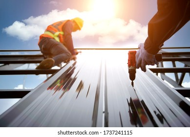Roofer works on the roof structure of a building at a construction site. Roofer uses an air gun or air gun and install Metal Sheet on a new roof in Asia.