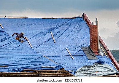 The roofer works on roof when is rain. The tarp covers the roof of the old house in the reconstruction.
