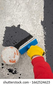 Roofer's hand in yellow mittens holding a brush with bituminous mastic. Waterproofing
