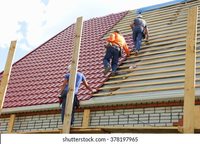 Roofers make the roof of metal tile