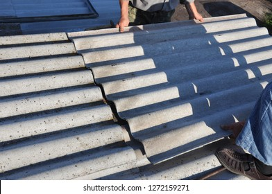 Roofers repair roof and remove asbestos old roof tiles. Roofing construction.